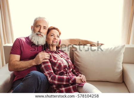 Happy mature couple in love sitting embracing on sofa at home