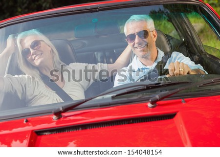 Happy mature couple in red cabriolet going for a ride on sunny day - stock photo