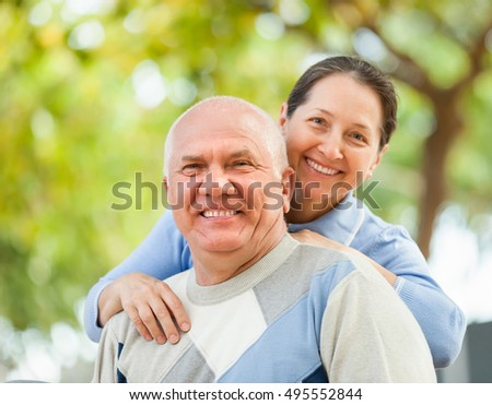 Happy mature couple in sweaters in autumn park