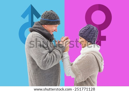 Happy mature couple in winter clothes embracing against pink and blue - stock photo