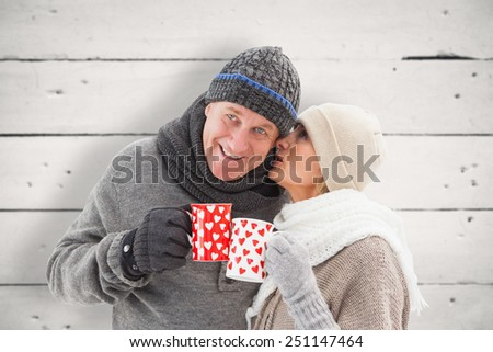 Happy mature couple in winter clothes holding mugs against white wood - stock photo