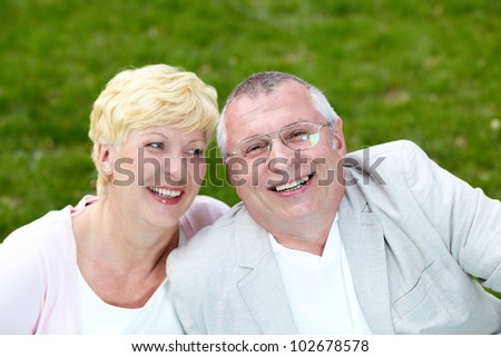 Happy mature couple laughing while having rest outside - stock photo