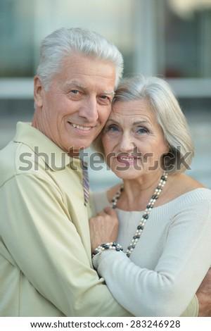 Happy mature couple near wall on street - stock photo