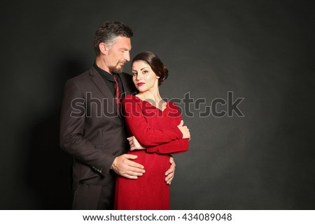Happy mature couple on dark background