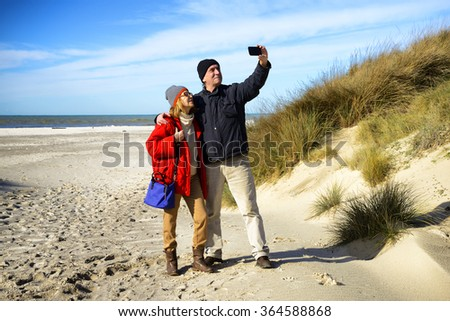 Happy mature couple on the beach - stock photo