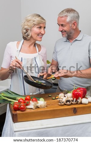 Happy mature couple preparing food together in the kitchen at home