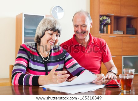 Happy mature couple reading financial documents in home interior