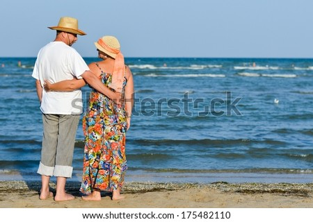 Happy mature couple resting at seashore on sandy beach and embracing - stock photo