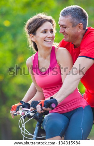 happy mature couple riding a bicycle in the green park - stock photo