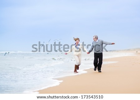 Happy mature couple running at a beautiful winter beach with seagulls - stock photo