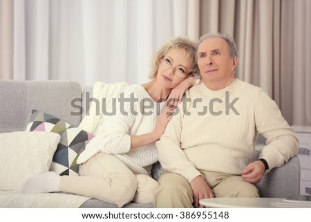 Happy mature couple sitting on a sofa together at home