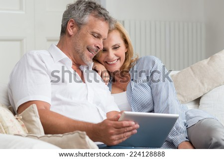 Happy Mature Couple Sitting On Sofa With Digital Tablet - stock photo