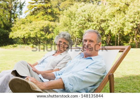 Happy mature couple sitting on sun loungers in park looking at camera - stock photo