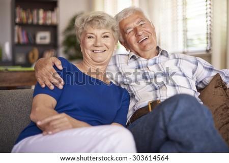 Happy mature couple sitting on the sofa - stock photo