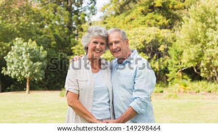 Happy mature couple smiling and looking at camera in park holding hands - stock photo