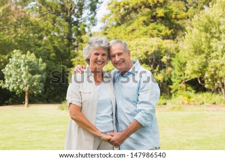 Happy mature couple smiling and looking at camera in the park - stock photo