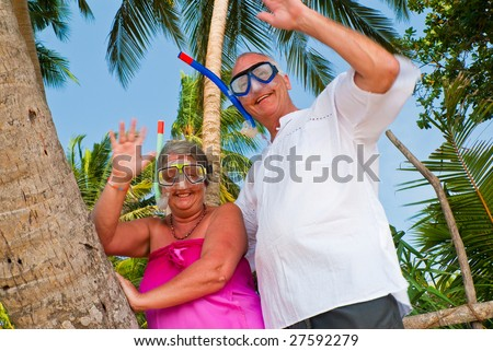 Happy mature couple smiling and waving in the shade of palm trees on the beach. They are wearing snorkeling gear and in the background is the blue sky with palms. - stock photo