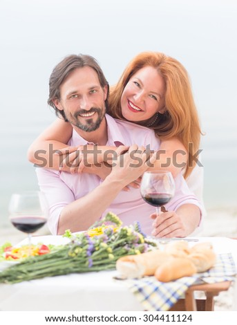 Happy mature couple smiling for the camera and looking at it. Man and woman resting in the restaurant nera by sea.