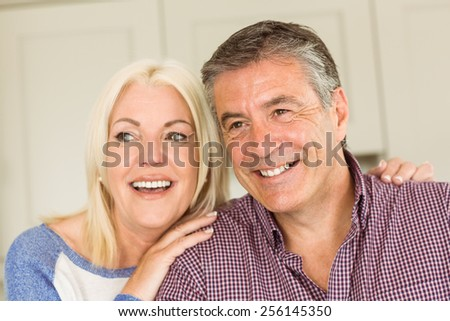Happy mature couple smiling together at home in the kitchen - stock photo