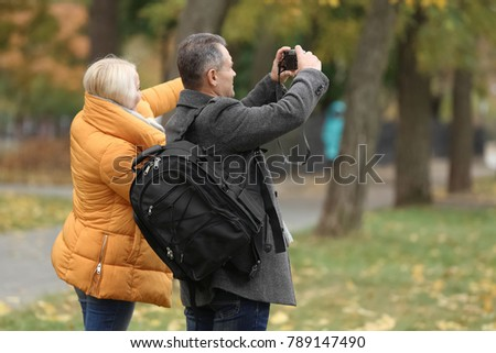 Happy mature couple taking photo in park