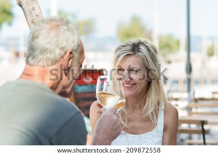 Happy mature couple toasting each other as they celebrate a summer vacation with white wine as they sit at an outdoor table at an open-air restaurant - stock photo