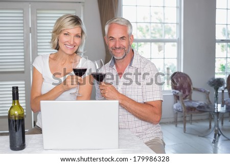 Happy mature couple toasting wine glasses while using laptop at home - stock photo