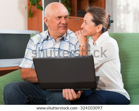 Happy mature couple together at the  laptop
