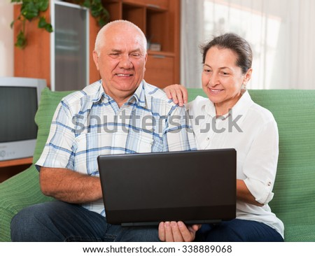 Happy mature couple together at the notebook - stock photo