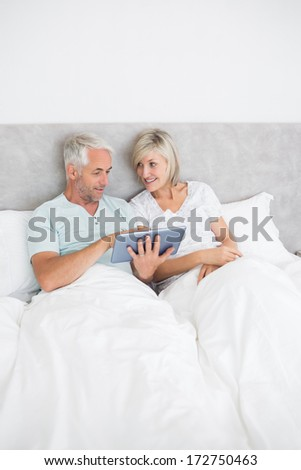 Happy mature couple using digital tablet in bed at home