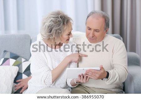 Happy mature couple using tablet together on a sofa at home