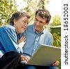 Happy mature couple using the laptop, outdoors, closeup - stock photo