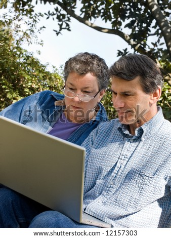 Happy mature couple using the laptop, outdoors, closeup - stock photo