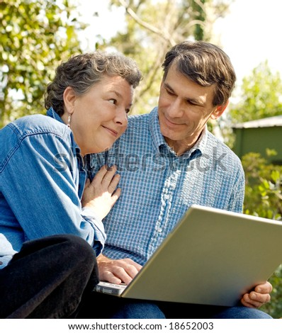 Happy mature couple using the laptop, outdoors, closeup