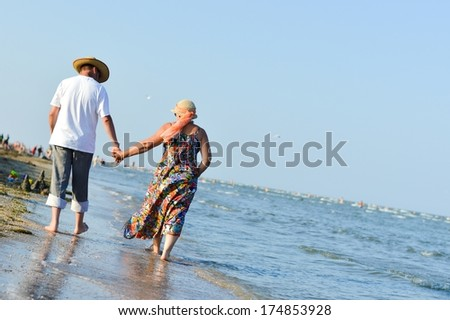Happy mature couple walking at seashore on sandy beach and embracing - stock photo