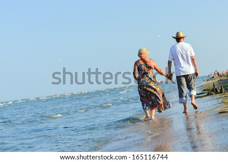 Happy mature couple walking at seashore on sandy beach and embracing on summer sea outdoors background - stock photo