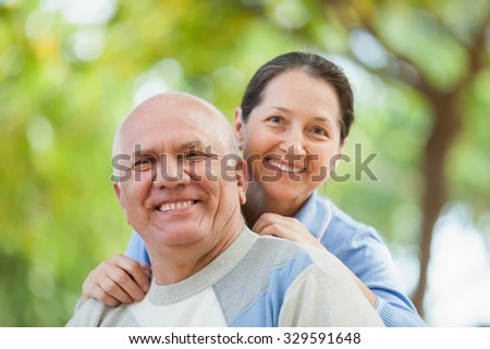 Happy mature couple walking in autumn park