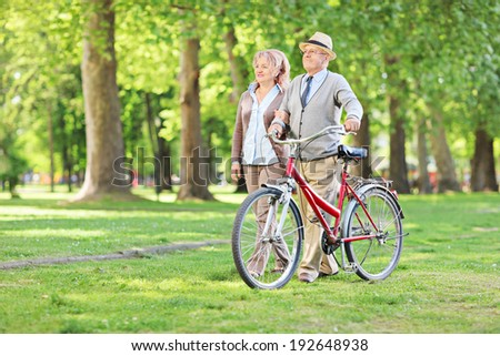 Happy mature couple walking in park and pushing a bike - stock photo