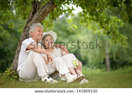 happy Mature couple walks in the park in summer day - stock photo