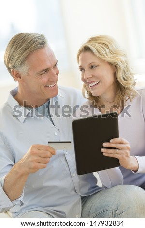 Happy mature couple with digital tablet and credit card looking at each other while shopping online - stock photo