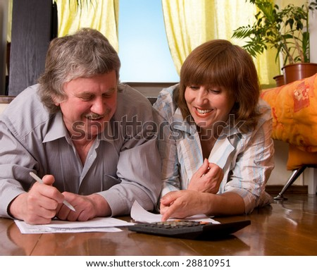 Happy mature couple with documents at home - stock photo