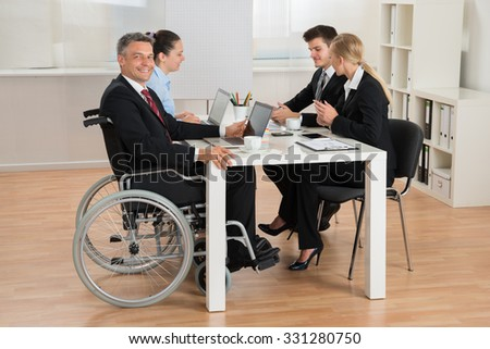 Happy Mature Disabled Businessman Having Meeting With Colleagues In Office - stock photo