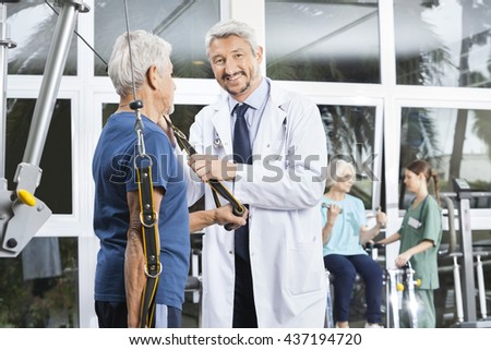 Happy Mature Doctor Assisting Senior Man With Resistance Band - stock photo