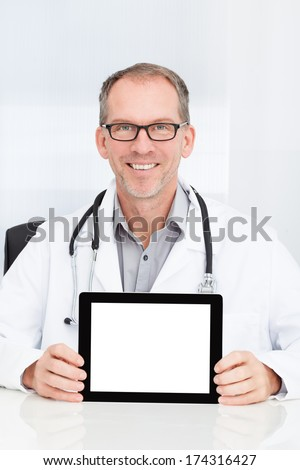 Happy Mature Doctor Showing Blank Digital Tablet In Clinic