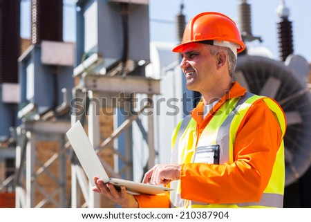 happy mature electrician using laptop - stock photo