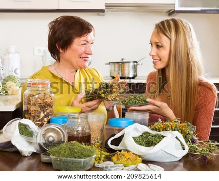 Happy mature female with daughter with dried herbs