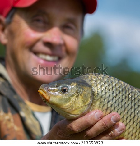 Happy mature fisherman holding his trophy carp (Cyprinus carpio). Focus on the fish