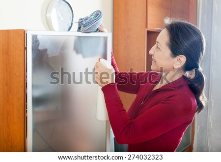 Happy mature housewife dusting glass on furniture with rag and cleanser at home