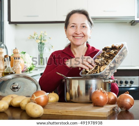 happy  mature housewife holding  dried mushrooms in home kitchen