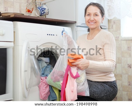 Happy mature housewife loading the washing machine with laundry bag