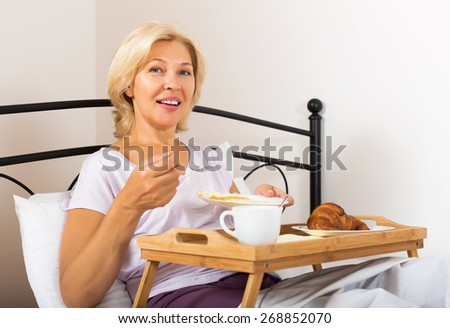 Happy mature lady has fried eggs and coffee for breakfast in bedroom